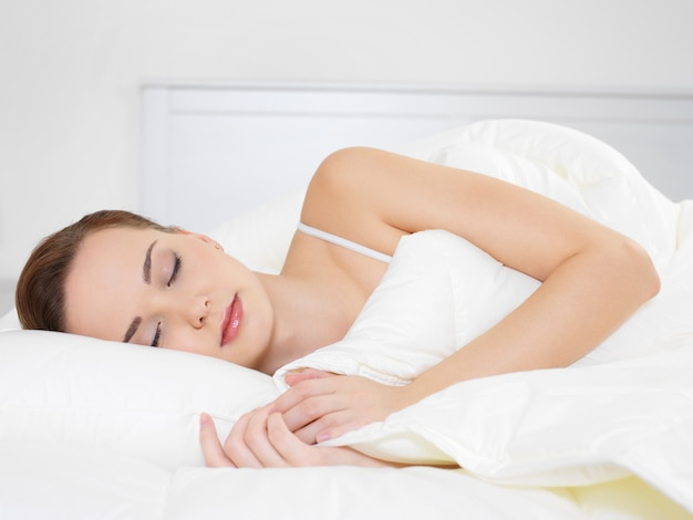 Młoda piękna kobieta śpi leżąc na boku w sypialni