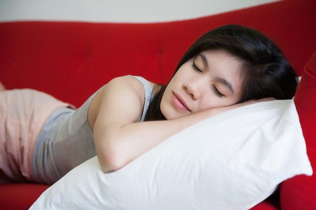 Młoda piękna kobieta śpi na czerwonej kanapie