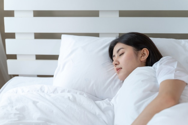 Młoda piękna kobieta śpi na łóżku