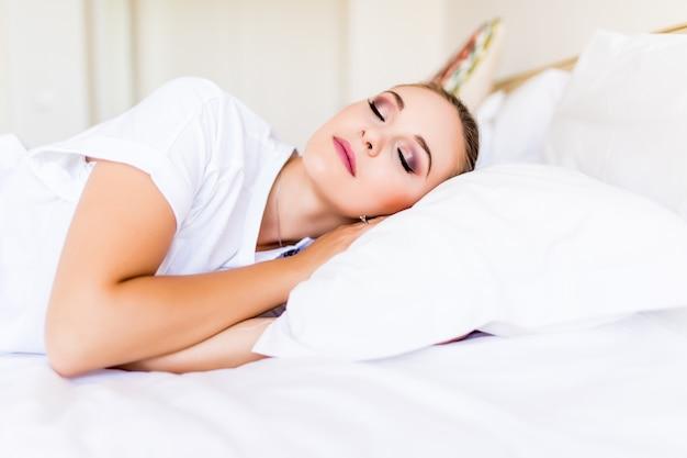 Młoda piękna kobieta śpi w łóżku i relaksując się rano