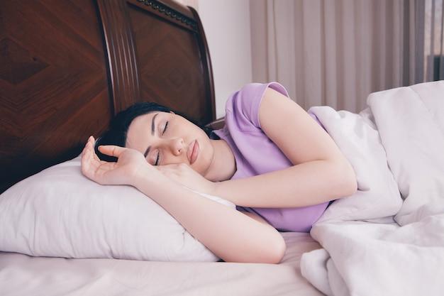 Młoda piękna kobieta śpi w łóżku
