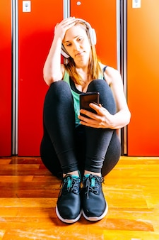 Młoda piękna kobieta sportowiec fit patrząc na smartfona ze słuchawkami muzycznymi w szatni siłowni