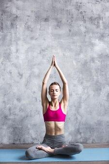 Młoda piękna kobieta sportowy, rozciągający się na matę do jogi
