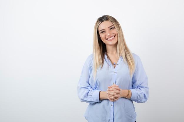 Młoda piękna kobieta stojąc na białej ścianie.
