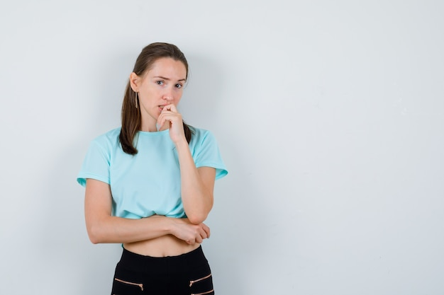 Młoda piękna kobieta stojąca w myśleniu pozie w t-shirt i patrząc zdziwiona, widok z przodu.