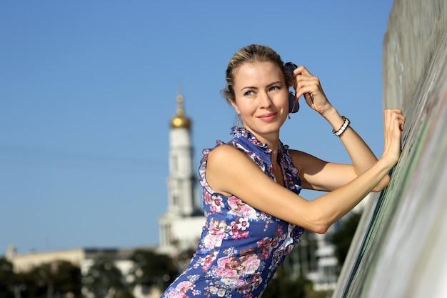 Młoda piękna kobieta stojąca w pobliżu betonowej ściany