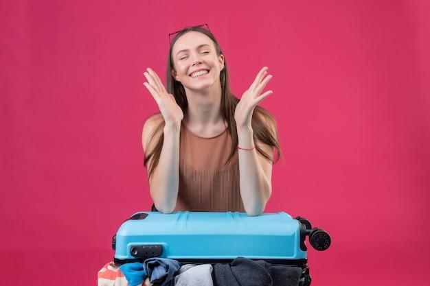 Młoda piękna kobieta stojąca z walizką podróżną z zamkniętymi oczami, uśmiechając się i zastanawiając się nad różowym tłem