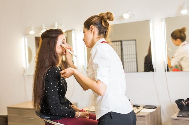 Młoda piękna kobieta stosująca makijaż przez wizażystę
