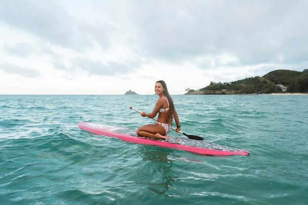 Młoda piękna kobieta surfuje na hawajach