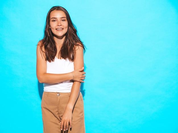 Młoda piękna kobieta szuka. modna dziewczyna w letnie ubrania na co dzień. śmieszna i pozytywna kobieta pozuje blisko błękit ściany