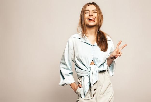 Młoda piękna kobieta szuka. modna dziewczyna w letnie ubrania. pozytywny zabawny model. pokazano język i znak pokoju