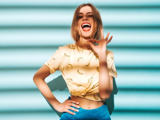 Młoda piękna kobieta szuka. modna dziewczyna w luźnych letnich żółtych koszulkach. śmieszny model pozuje blisko błękit ściany. pokazywać ok znaka ręką i palcami.