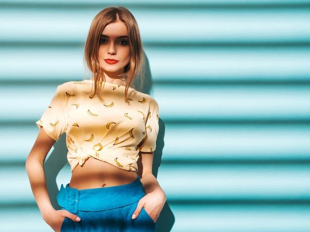 Młoda piękna kobieta szuka. modna dziewczyna w luźnych letnich żółtych koszulkach. wzorcowy pozować blisko błękit ściany