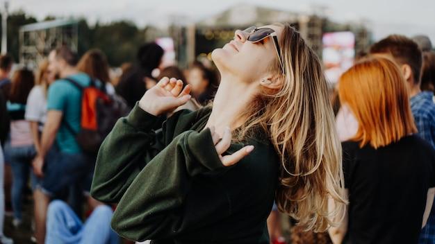 Młoda piękna kobieta tańczy na festiwalu muzycznym