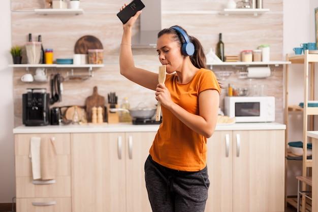Młoda piękna kobieta tańczy podczas słuchania muzyki w niebieskich słuchawkach bezprzewodowych w kuchni