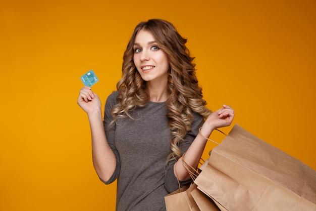 Młoda piękna kobieta torby na zakupy i karty kredytowej samodzielnie na żółtym tle