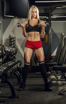 Młoda piękna kobieta, trening na siłowni.