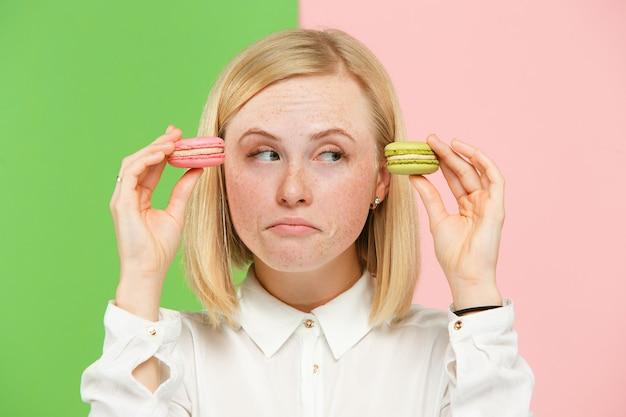 Młoda piękna kobieta trzyma ciasto makaroniki w dłoniach, modne kolorowe w studio.