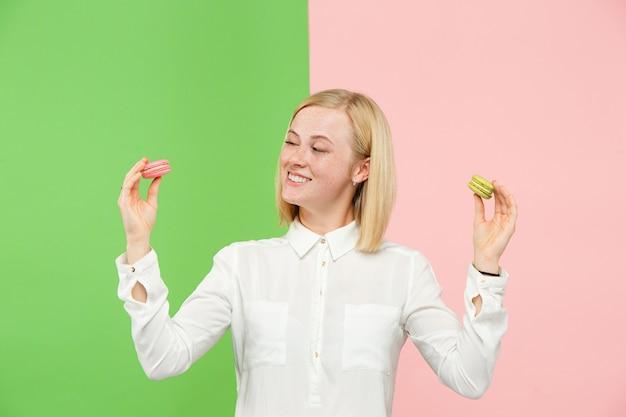 Młoda piękna kobieta trzyma ciasto makaroniki w dłoniach, na modnym kolorowym tle w studio.