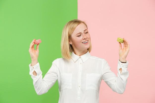 Młoda piękna kobieta trzyma ciasto makaroniki w dłoniach