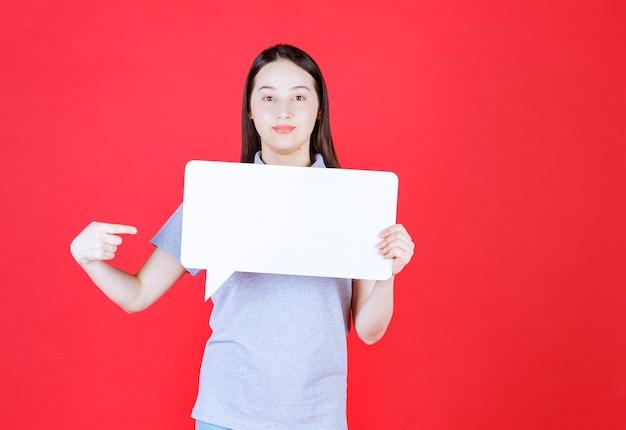 Młoda piękna kobieta trzyma deskę i wskazuje na niej palec