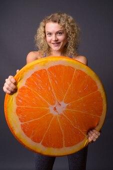 Młoda piękna kobieta trzyma duży kawałek pomarańczy