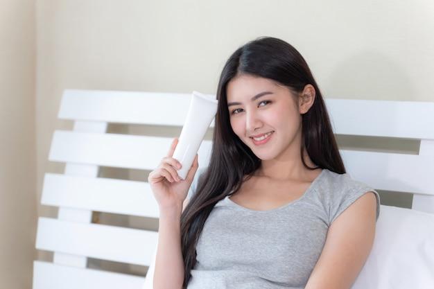 Młoda piękna kobieta trzyma i balsam do skóry w dłoni i uśmiecha się ze szczęścia