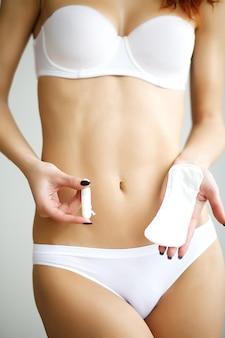 Młoda piękna kobieta trzyma menstruacyjny bawełniany tampon i uszczelkę w jej ręce, w białej bieliźnie