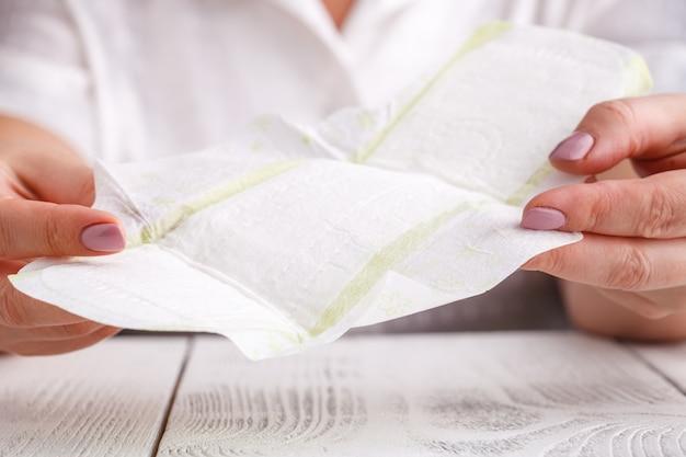 Młoda piękna kobieta trzyma miesiączkowego bawełnianego tampon i uszczelkę w jej ręce