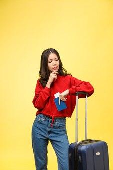 Młoda piękna kobieta trzyma paszport, patrząc zamyślony