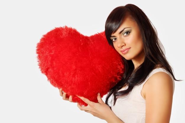 Młoda piękna kobieta trzyma poduszkę w kształcie serca
