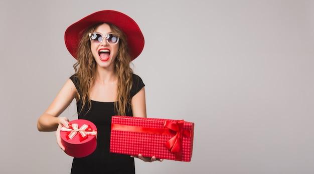 Młoda piękna kobieta trzyma prezenty, czarna sukienka, czerwony kapelusz, okulary przeciwsłoneczne, szczęśliwa, uśmiechnięta, seksowna, elegancka, pudełka na prezenty, świętuje, pozytywna, emocjonalna