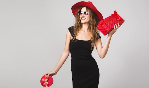 Młoda piękna kobieta trzyma prezenty, czarna sukienka, czerwony kapelusz, okulary przeciwsłoneczne, szczęśliwa, uśmiechnięta, seksowna, elegancka, pudełka na prezenty, świętuje, pozytywne