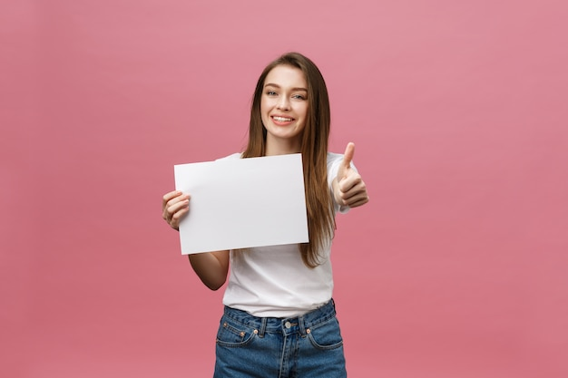 Młoda piękna kobieta trzyma pustą kartę i pokazuje kciuki do góry