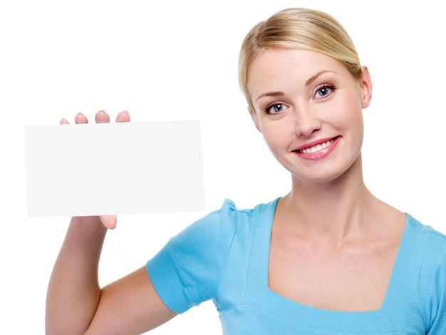 Młoda piękna kobieta trzyma pustą wizytówkę w pobliżu jej twarzy - na białym