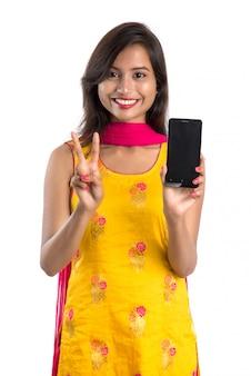 Młoda piękna kobieta trzyma pustego ekranu smartphone i pokazuje, telefon komórkowy, pastylka lub telefon na białym tle.