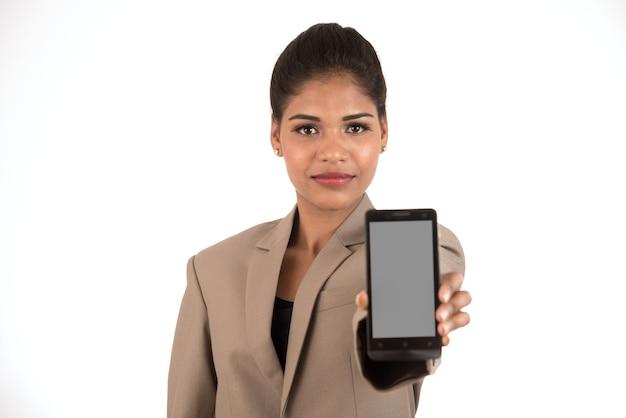 Młoda piękna kobieta trzyma pusty ekran inteligentny telefon na białym tle