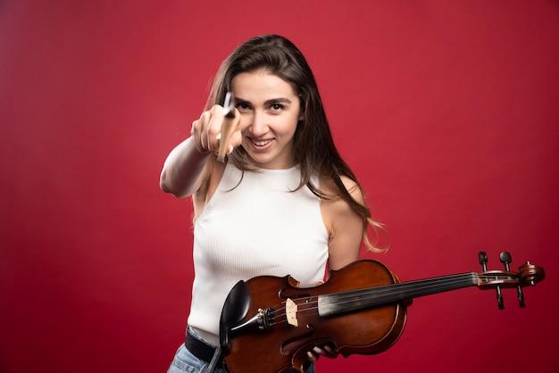 Młoda piękna kobieta trzyma skrzypce