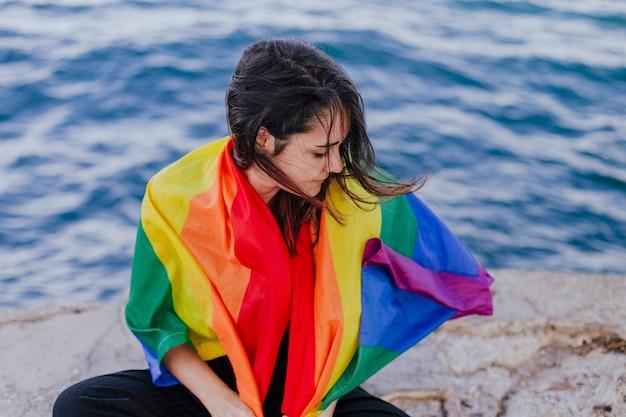 Młoda piękna kobieta trzyma tęczową homoseksualistę flaga outdoors