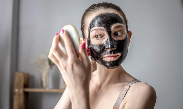 Młoda piękna kobieta trzyma w dłoni lusterko i zdejmuje z twarzy kosmetyczną czarną maskę