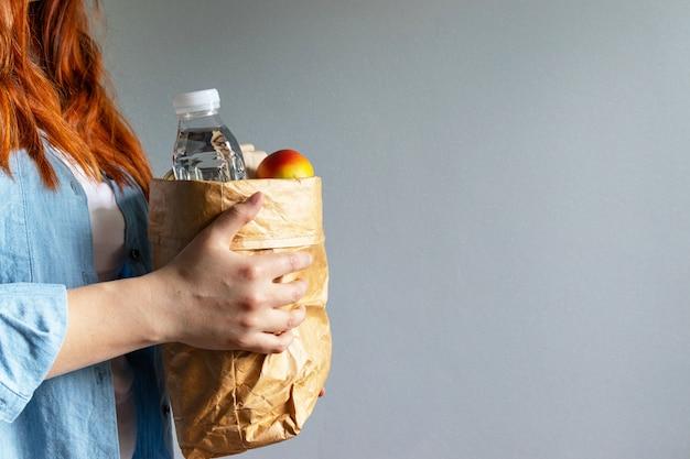 Młoda piękna kobieta trzyma zabiera papierową torbę zdrowej żywności od dostawy