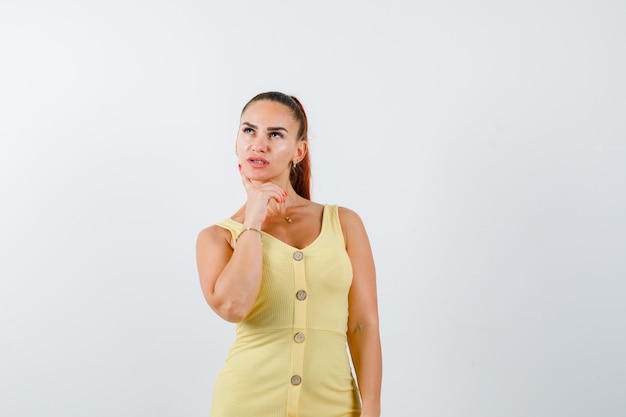 Młoda piękna kobieta trzymając palec na policzku w sukience i patrząc zamyślony. przedni widok.