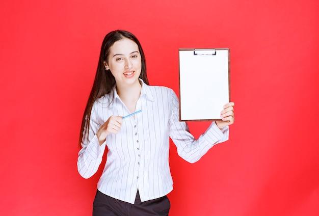 Młoda piękna kobieta trzymając pusty schowek na czerwonej ścianie.