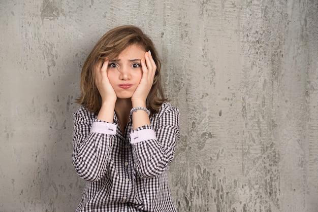 Młoda piękna kobieta trzymając się za ręce na głowie