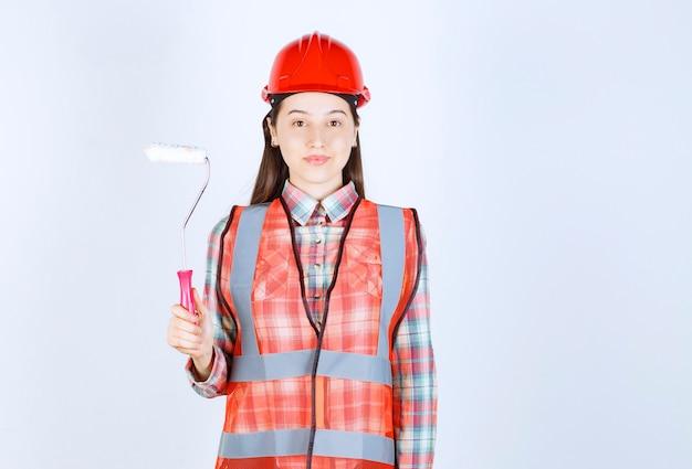 Młoda piękna kobieta trzymając wałek do malowania naprawy ścian.