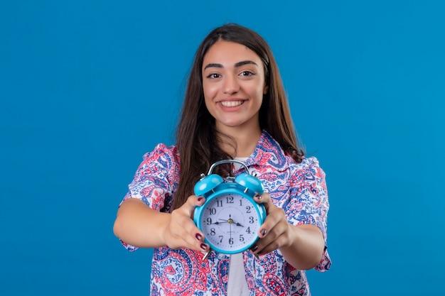 Młoda piękna kobieta turysta trzyma budzik z szczęśliwą twarzą stojącą i uśmiechając się na na białym tle niebieskim tle