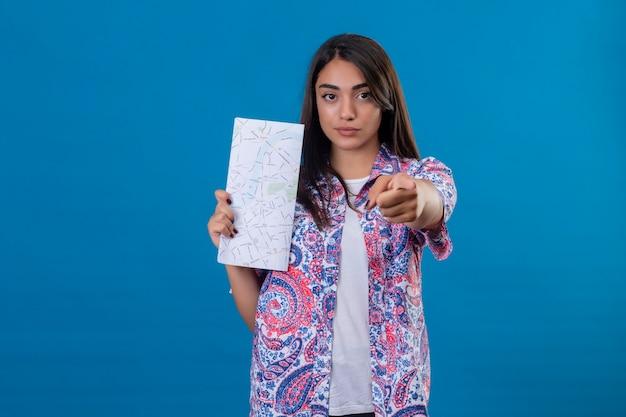 Młoda piękna kobieta turysta trzyma mapę wskazując na aparat z palcem wskazującym z pewną poważną miną na twarzy stojącej na na białym tle niebieskim tle
