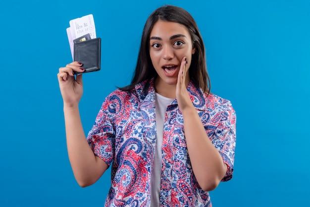 Młoda piękna kobieta turysta trzyma paszport z biletami patrząc na kamery, mówiąc tajemnicę ręką w pobliżu ust stojących na na białym tle niebieskim tle