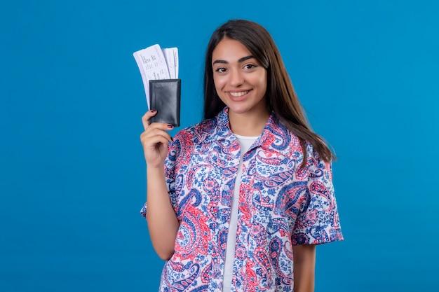Młoda piękna kobieta turysta trzyma paszport z biletami patrząc na kamery uśmiechnięty wesoło gotowy do wakacji stojących na na białym tle niebieskim tle