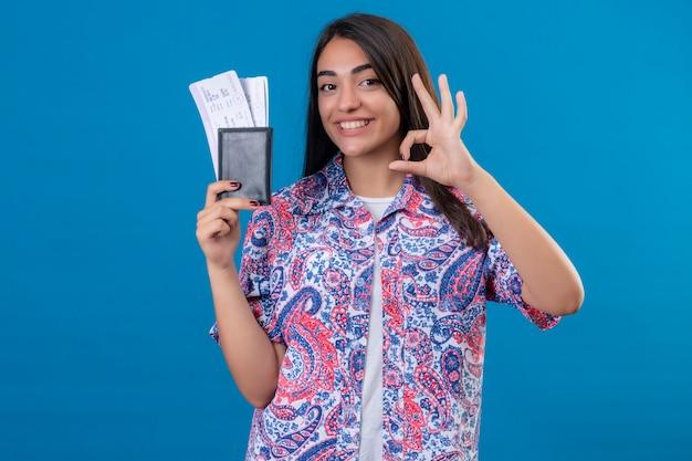 Młoda piękna kobieta turysta trzyma paszport z biletów patrząc na kamery uśmiechnięty radośnie robi ok znak stojąc na na białym tle niebieskim tle